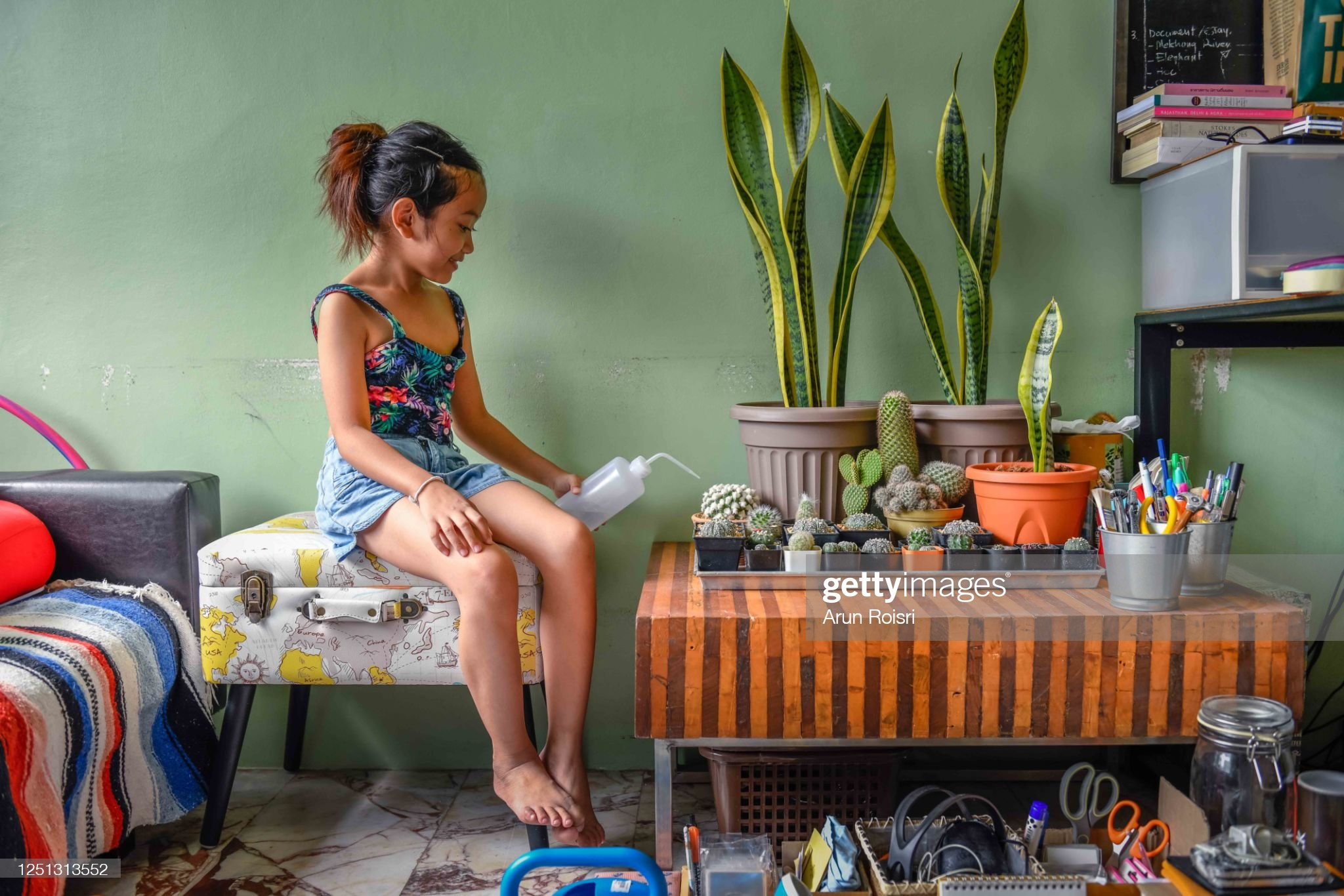Adorable asian girl watering plants in green living room : 圖庫照片