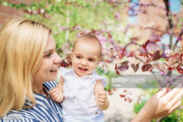 Adorable baby and mother in park, close up portrait