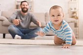 Adorable baby boy crawling on floor with dad