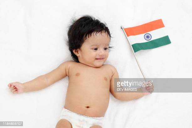 adorable baby boy holding tricolor indian flag - indian flag stock pictures, royalty-free photos & images
