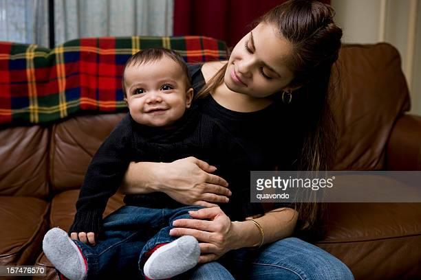 Adorable bébé garçon assis sur Latina mère tour à la maison