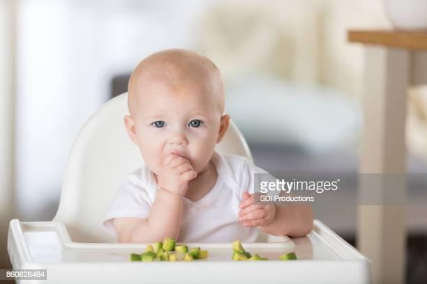 Adorable niña alimenta a sí misma un aguacate