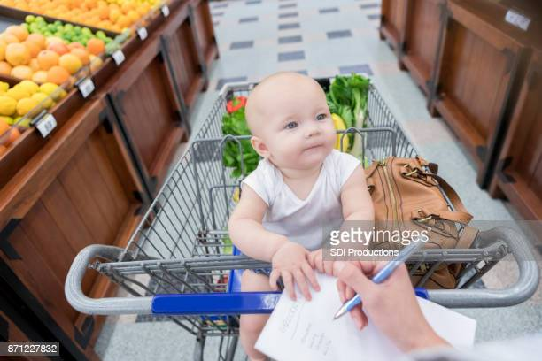 Adorable baby girl looks up at her mom while they shop for groceries
