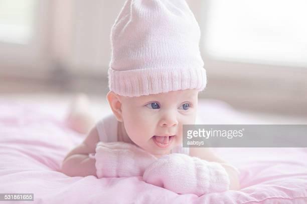 Encantadores baby girl lying en su estómago Riendo