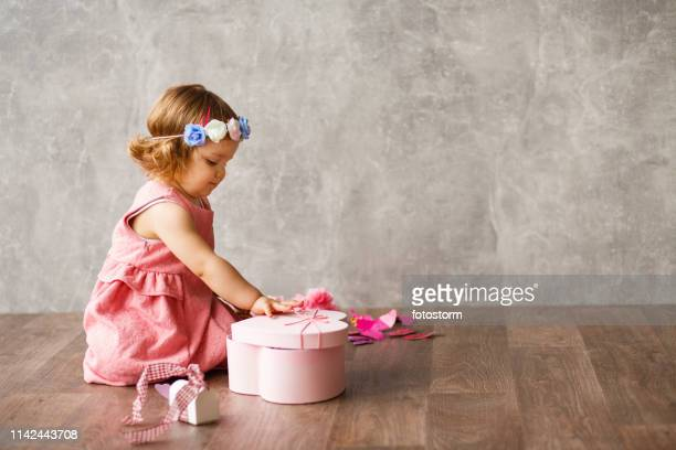 adorable baby girl opening a gift - babyhood stock pictures, royalty-free photos & images