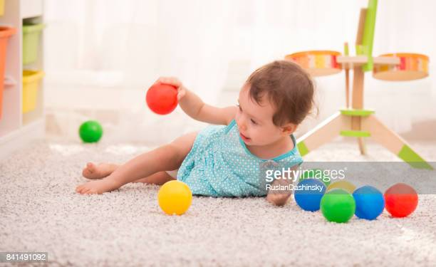 adorable baby girl playing with colorful balls at home. - lying on side stock pictures, royalty-free photos & images