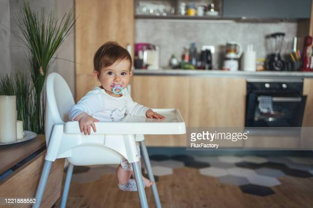 adorable baby girl sitting in her high chair with pacifier in her mouth - eczema stock pictures, royalty-free photos & images