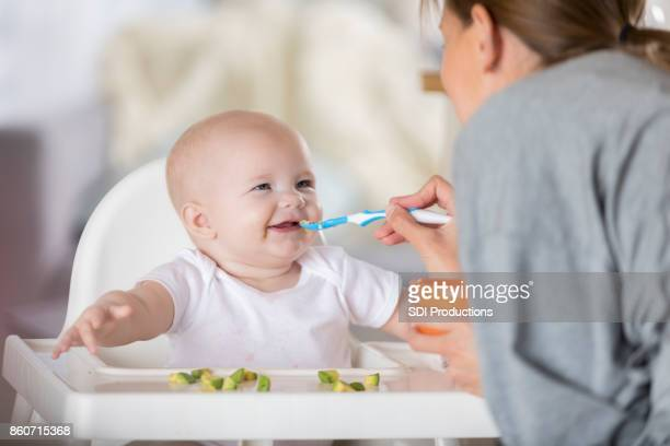 Adorable baby in high chair laughs while being spoon fed