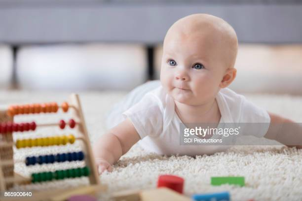 Adorable baby plays on floor in living room