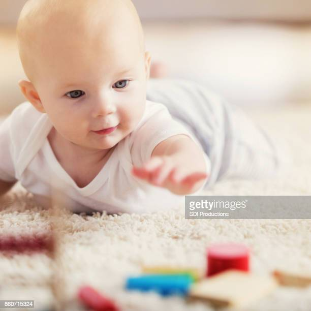 Adorable baby reaches for wooden blocks during tummy time
