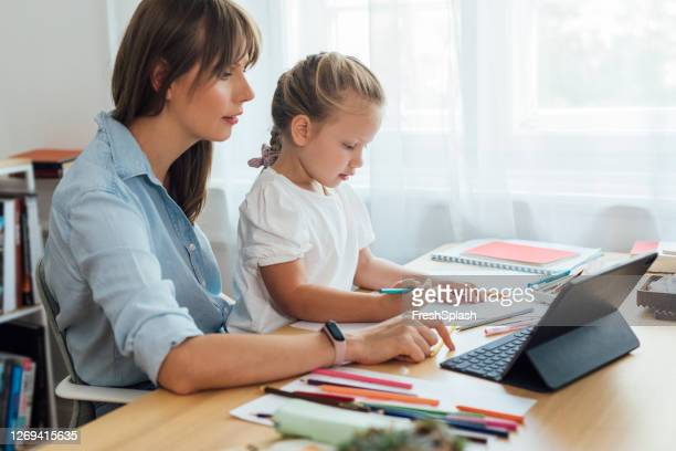 adorable blonde girl drawing with the help of her mother; they're watching a video tutorial together - nursery school child stock pictures, royalty-free photos & images