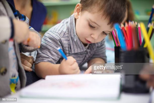 adorable boy drawing with color pencil at playschool - preschool age stock pictures, royalty-free photos & images