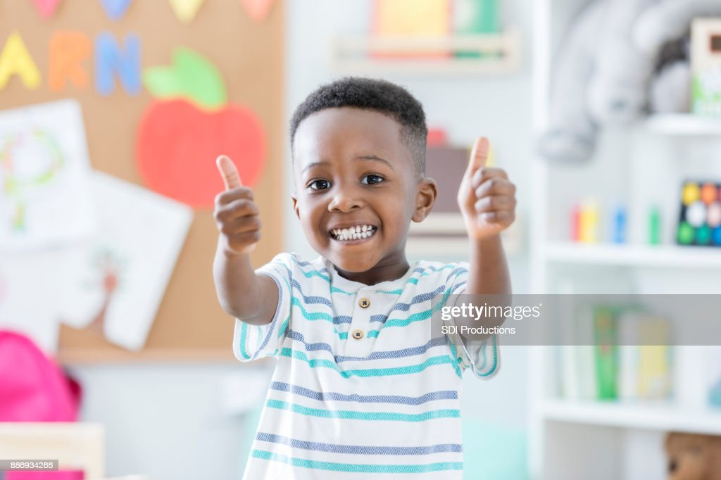 Adorable boy gives thumbs up in preschool : Stock Photo