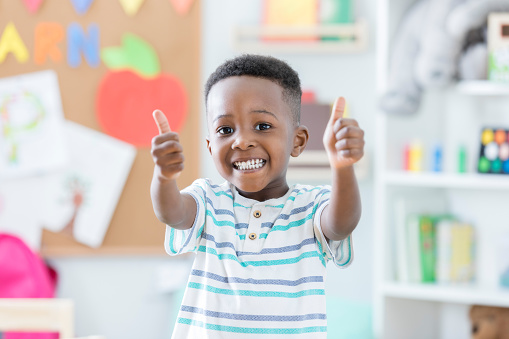 Adorable boy gives thumbs up in preschool 886934266