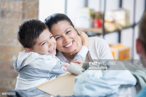 adorable boy hugs his mom while donating items to homeless shelter - homeless shelter stock pictures, royalty-free photos & images