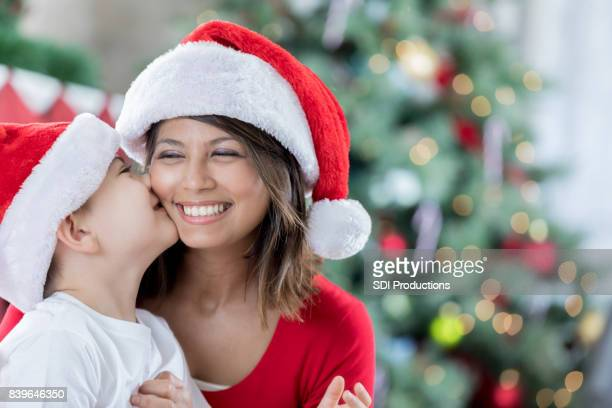 adorable boy kisses mom on christmas morning - filipino christmas family stock pictures, royalty-free photos & images