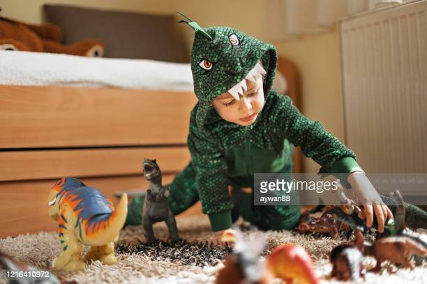 adorable boy playing with his dinosaurs - dinosaur stock pictures, royalty-free photos & images