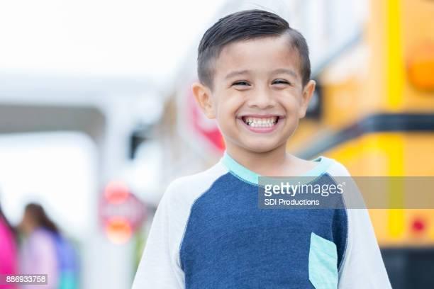 Adorable boy smiles before boarding school bus