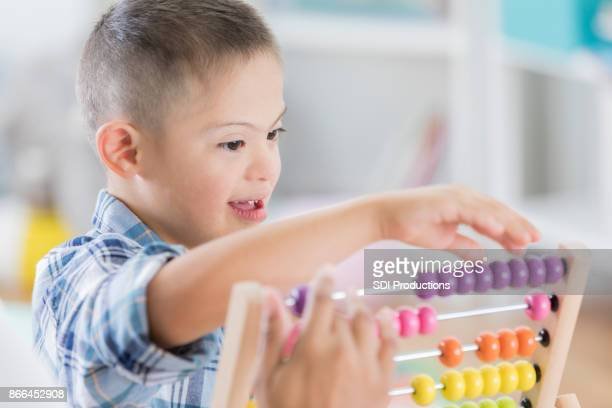 Adorable boy with Down Syndrome plays with abacus