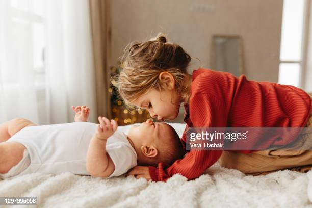 adorable child kissing little sister lying on white bedding - genderblend stock pictures, royalty-free photos & images