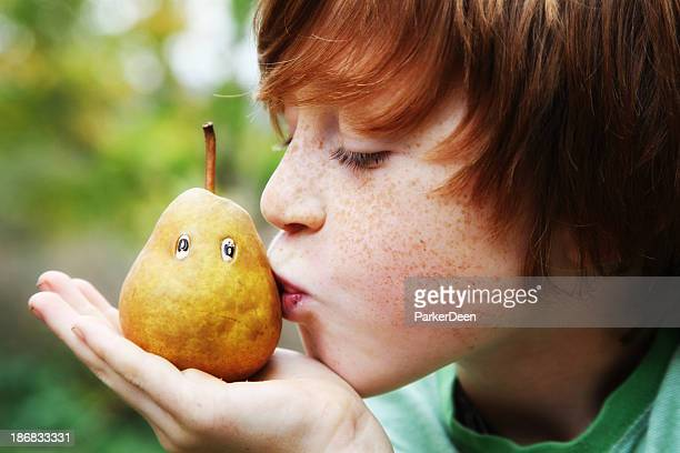 Adorable Child Kissing Organic Pear with a Face