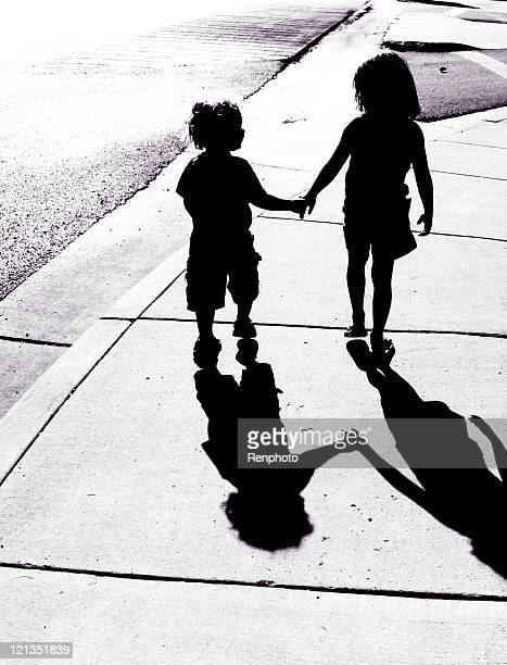 Adorable Children Silhouettes: Boy and Girl Holding Hands