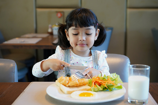 Adorable cute Asian kid having a healthy breakfast in the morning. - gettyimageskorea