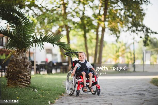車椅子の愛らしい障害のある少年 - 麻痺 ストックフォトと画像