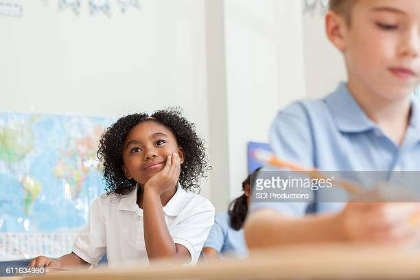Adorable elementary student daydreams in class