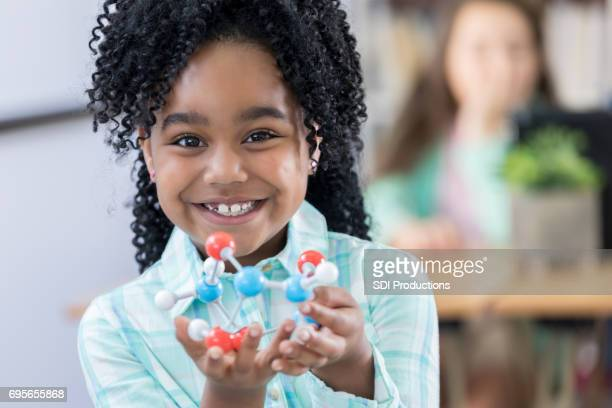 adorable elementary student showing molecular structure model - atom stock photos and pictures