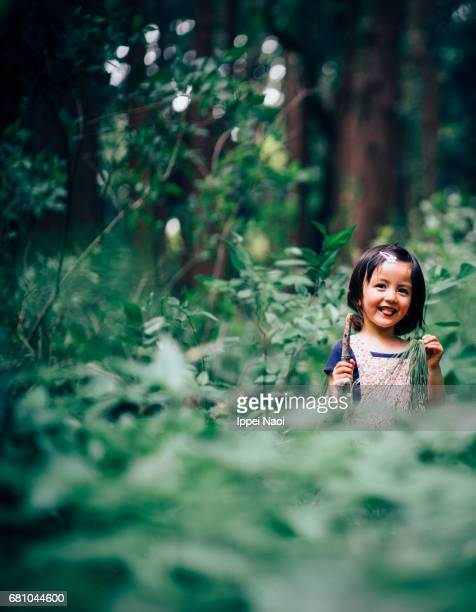 Adorable Eurasian little girl smiling at camera in nature
