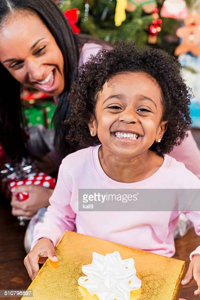 adorable, excited african american child with parent holding christmas present - little girl giving head stock photos and pictures