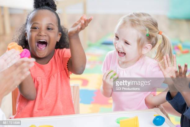 Adorable excited preschool girls at school