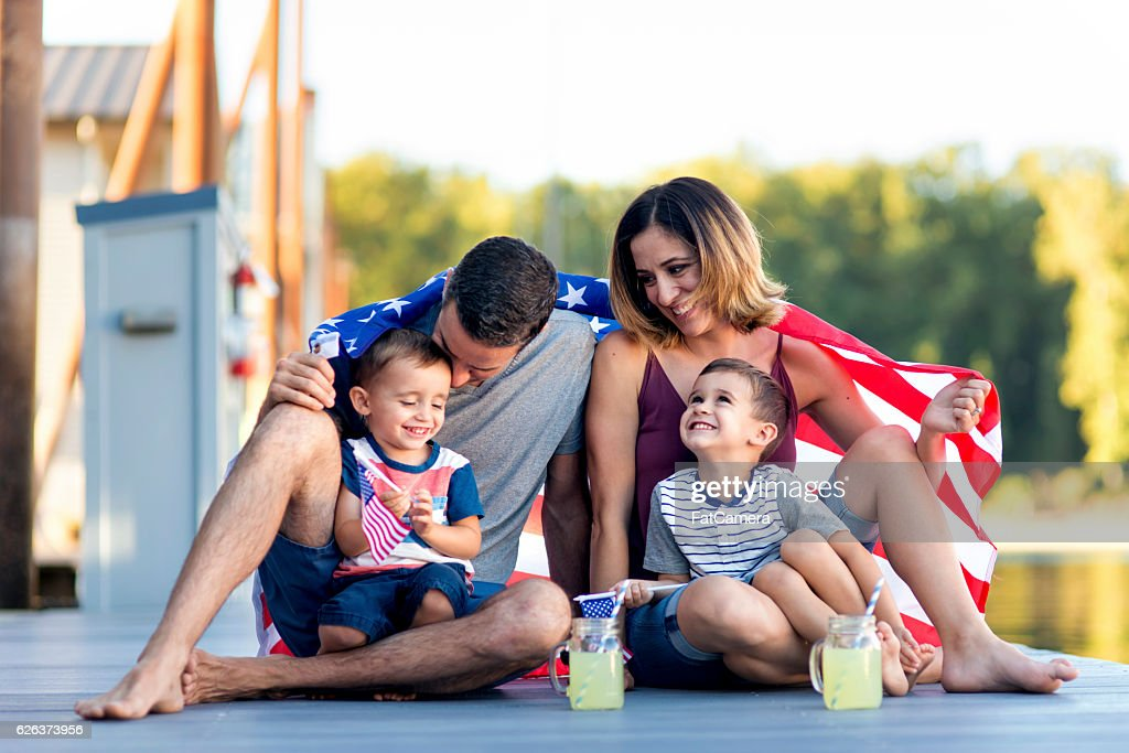 Adorable family of four together on Independence Day : Stock Photo