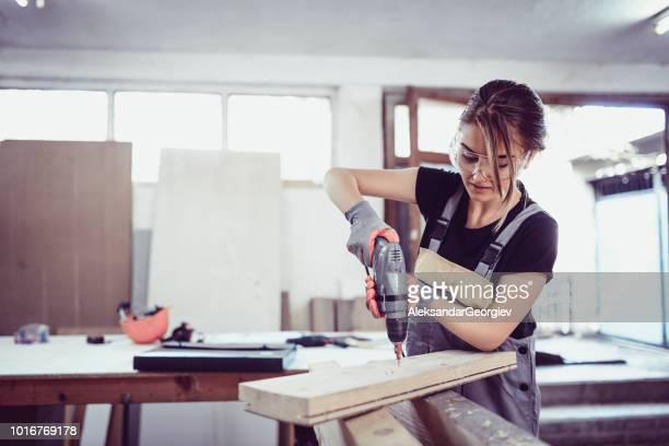 Adorable Female Carpenter Drilling In Wooden Block