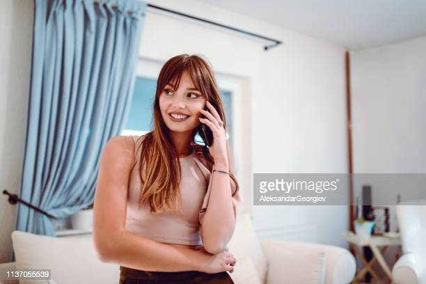 Adorable Female Teenager Talking On Phone In Living Room