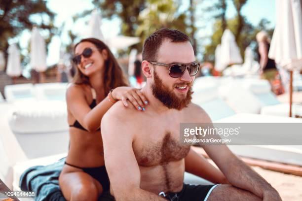 Adorable Girl Giving a Beach Massage To Her Boyfriend