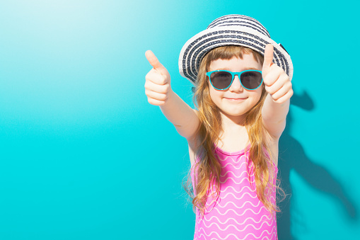 Adorable girl in swimsuit showing thumbs up 948973630