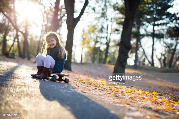 Adorable girl is sitting on a skateboard