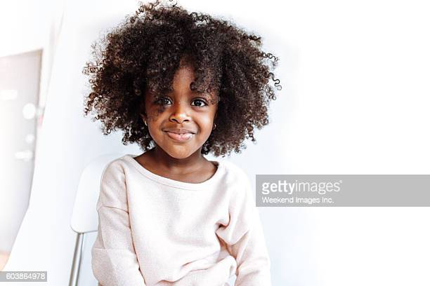 adorable girl looking at camera - afro frisur stock-fotos und bilder
