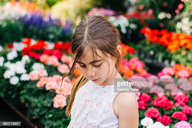Adorable girl looking down surrounded by flowers
