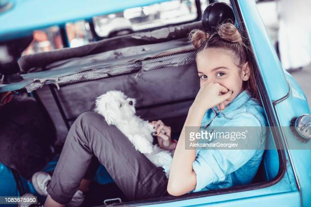 Adorable Girl Posing With Her Pet Puppy In Vintage Car Trunk