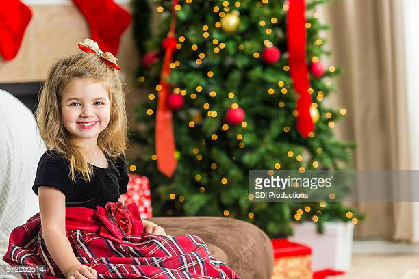 adorable girl ready to open presents at a christmas party - innocence stock pictures, royalty-free photos & images