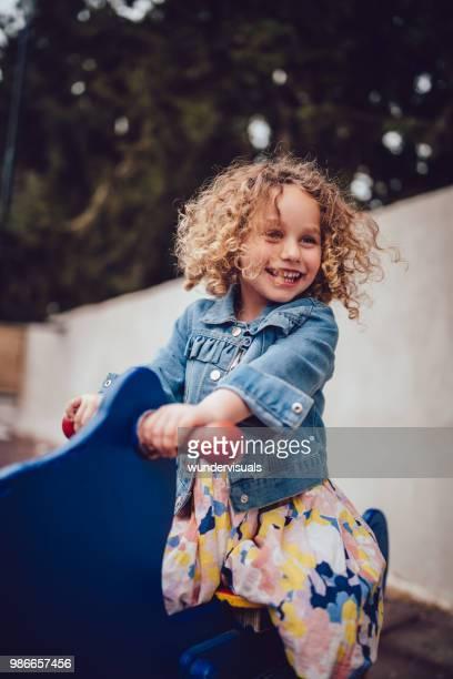 adorável menina com cabelo loiro encaracolado, brincar no parque infantil - infância - fotografias e filmes do acervo