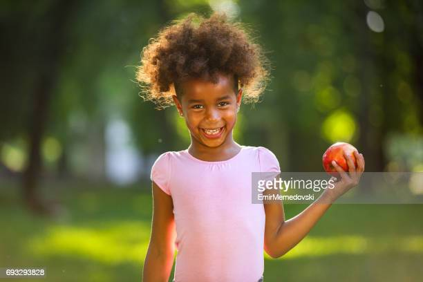 Adorable girl with red apple smiling at the camera