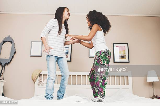 Adorable girls jumping in bed at home