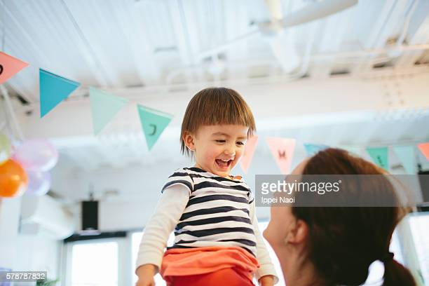 Adorable happy 2 year old girl with her mother at her birthday party