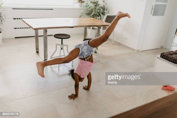 adorable kid doing cartwheel at the apartment - cartwheel stock pictures, royalty-free photos & images