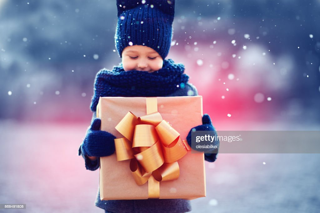 adorable kid with big gift box under a snowfall. Focus on gift box : Stock Photo