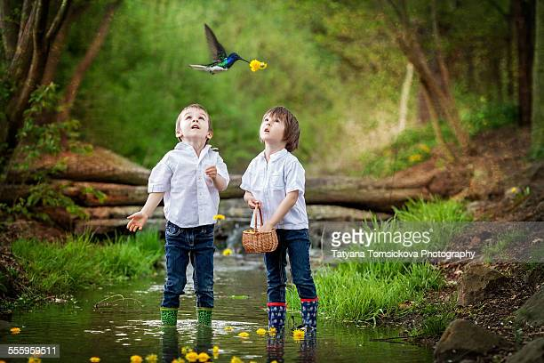 Adorable kids in a forest, playing with dandelions